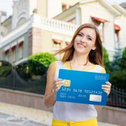 woman holding big banking card